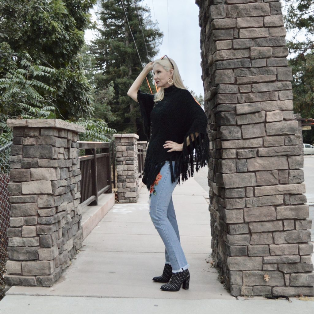 studded boots, poncho, distressed jeans