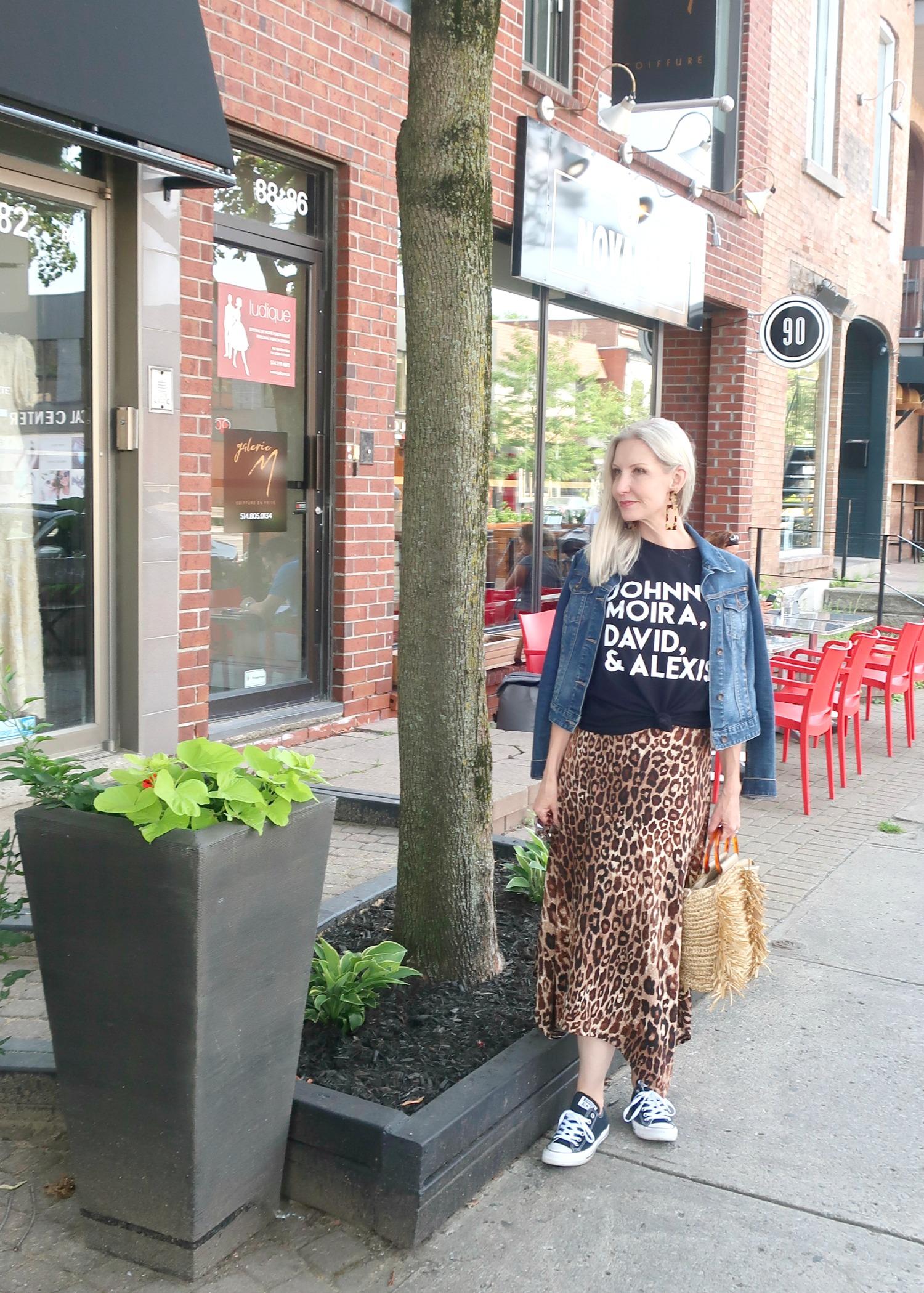 Schitt's Creek tee, leopard midi skirt, sneakers, denim jacket