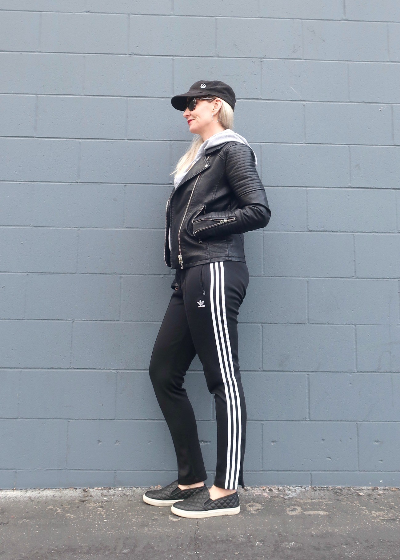 outfit idea with track pants, baseball cap, moto, hoodie